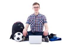 Adolescente hermoso que se sienta con el ordenador portátil, la mochila y vagos del fútbol Foto de archivo libre de regalías