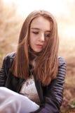 Adolescente hermoso que se sienta con soplar del pelo Foto de archivo libre de regalías