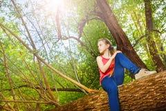 Adolescente hermoso que se sienta en árbol caido Foto de archivo