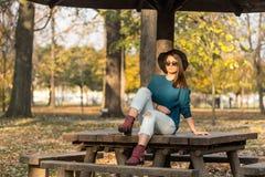 Adolescente hermoso que se sienta en el banco de parque con el suéter azul del sombrero negro y vaqueros rasgados con las hojas d Imagenes de archivo
