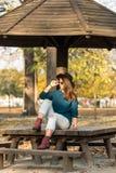 Adolescente hermoso que se sienta en el banco de parque con el suéter azul del sombrero negro y vaqueros rasgados con las hojas d Fotos de archivo libres de regalías