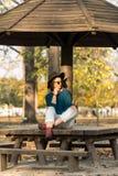 Adolescente hermoso que se sienta en el banco de parque con el suéter azul del sombrero negro y vaqueros rasgados con las hojas d Fotos de archivo