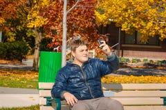 Adolescente hermoso que se sienta en el banco en parque y que hace la fotografía del uno mismo en su teléfono móvil Imagenes de archivo