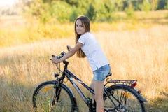Adolescente hermoso que se sienta en la bicicleta en el prado Imagen de archivo