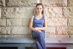Adolescente hermoso que se sienta en un banco de madera Imagen de archivo