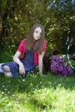 Adolescente hermoso que se sienta en un campo con una bicicleta con a Imágenes de archivo libres de regalías