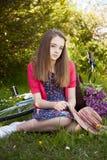 Adolescente hermoso que se sienta en un campo con una bicicleta con a Foto de archivo libre de regalías