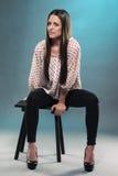Adolescente hermoso que se sienta en un taburete Foto de archivo