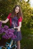 Adolescente hermoso que se sienta en una bicicleta con una cesta de flo Imagen de archivo libre de regalías