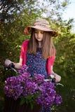 Adolescente hermoso que se sienta en una bicicleta con una cesta de flo Imagenes de archivo