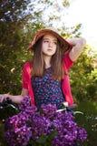 Adolescente hermoso que se sienta en una bicicleta con una cesta de flo Foto de archivo