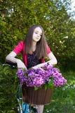 Adolescente hermoso que se sienta en una bicicleta con una cesta de flo Imagen de archivo