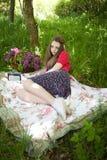 Adolescente hermoso que se sienta en una manta en arbolado Fotografía de archivo libre de regalías