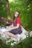 Adolescente hermoso que se sienta en una manta en un bosque Fotografía de archivo libre de regalías
