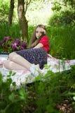 Adolescente hermoso que se sienta en una manta en un bosque Imagenes de archivo