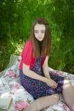 Adolescente hermoso que se sienta en una manta en un prado Imagen de archivo