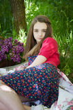 Adolescente hermoso que se sienta en una manta en un prado Fotografía de archivo