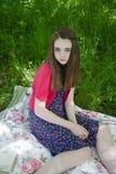 Adolescente hermoso que se sienta en una manta en un prado Foto de archivo libre de regalías