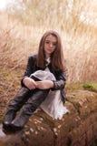 Adolescente hermoso que se sienta en una pared de piedra Foto de archivo