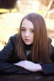 Adolescente hermoso que se sienta en una tabla con sus brazos doblados Fotografía de archivo