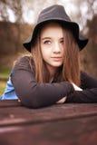 Adolescente hermoso que se sienta en una tabla con sus brazos doblados Fotos de archivo