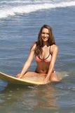 Adolescente hermoso que se sienta en una tabla hawaiana Foto de archivo libre de regalías