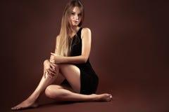 Adolescente hermoso que se sienta en vestido negro Fotos de archivo libres de regalías