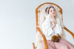 Adolescente hermoso que sonríe en la cámara mientras que se sienta en mecedora con los conejos peludos Imágenes de archivo libres de regalías