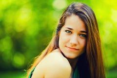 Adolescente hermoso que sonríe en un fondo verde Fotos de archivo libres de regalías