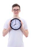 Adolescente hermoso que sostiene el reloj de la oficina aislado en blanco Imagen de archivo