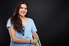 Adolescente hermoso que sostiene una pila de libros Fotos de archivo