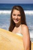 Adolescente hermoso que sostiene una tabla hawaiana en la sonrisa de la playa Foto de archivo