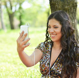 Adolescente hermoso que tiene una llamada video al aire libre Imagen de archivo