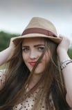 Adolescente hermoso que tira en su sombrero Fotografía de archivo libre de regalías