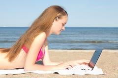 Adolescente hermoso que trabaja en el ordenador portátil en la playa Imagenes de archivo
