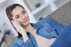 Adolescente hermoso que usa el teléfono elegante que se sienta en el sofá Fotografía de archivo libre de regalías
