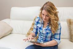 Adolescente hermoso que usa la PC de la tableta que se sienta en el sofá Fotografía de archivo