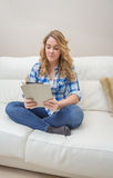 Adolescente hermoso que usa la PC de la tableta que se sienta en el sofá Imágenes de archivo libres de regalías
