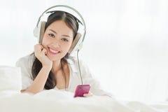 Adolescente hermoso que usa smartphone con el auricular en casa Imagenes de archivo