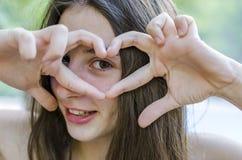 Adolescente hermoso relajado en sus días de fiesta que hacen un gestur del corazón Imagenes de archivo