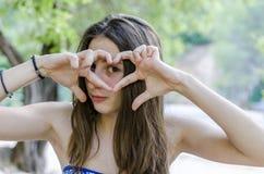 Adolescente hermoso relajado en sus días de fiesta que hacen un gestur del corazón Foto de archivo libre de regalías
