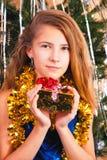 Adolescente hermoso satisfecho que abraza un regalo de la Navidad Fotografía de archivo libre de regalías