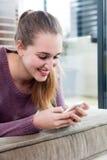 Adolescente hermoso sincero sonriente que mecanografía en su smartphone Foto de archivo
