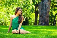 Adolescente hermoso Sitted sonriente en la hierba Imagen de archivo