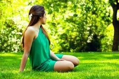 Adolescente hermoso Sitted sonriente en la hierba Imagenes de archivo