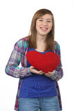 Adolescente hermoso sonriente con un corazón rojo en la D de la tarjeta del día de San Valentín Imagen de archivo libre de regalías
