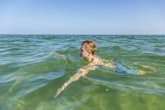 Adolescente hermoso tiene natación de la diversión en el océano Fotografía de archivo