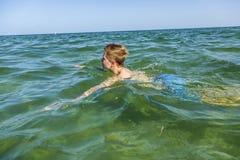 Adolescente hermoso tiene natación de la diversión en el océano Foto de archivo