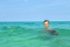 Adolescente hermoso tiene natación de la diversión en el océano Fotos de archivo libres de regalías