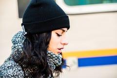 Adolescente hermoso triste con el sombrero negro y la capa gris - vista lateral Fotos de archivo